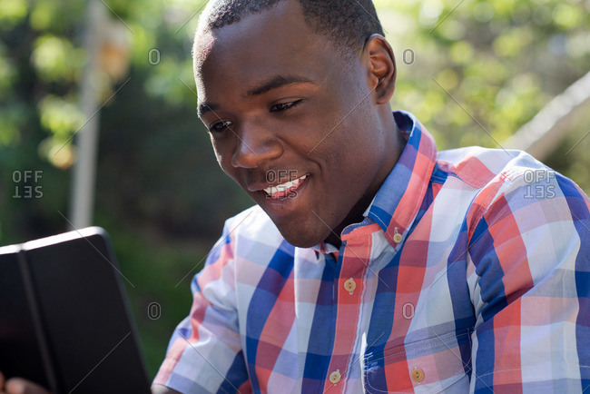 A young man looks at a tablet while sitting outside