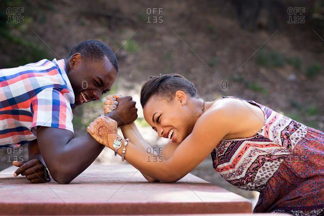 A woman arm wrestles her boyfriend