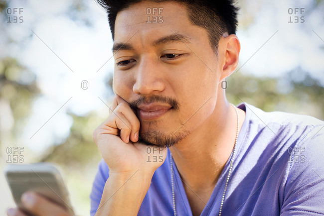 A young man stares at his phone