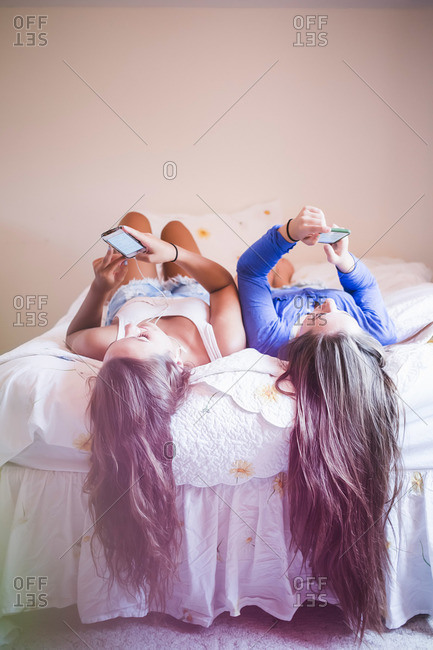 Two teen girls with long hair hanging off the bed occupied with their smartphones