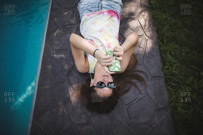 Overhead view of teenaged girl lounging next to pool with her smartphone