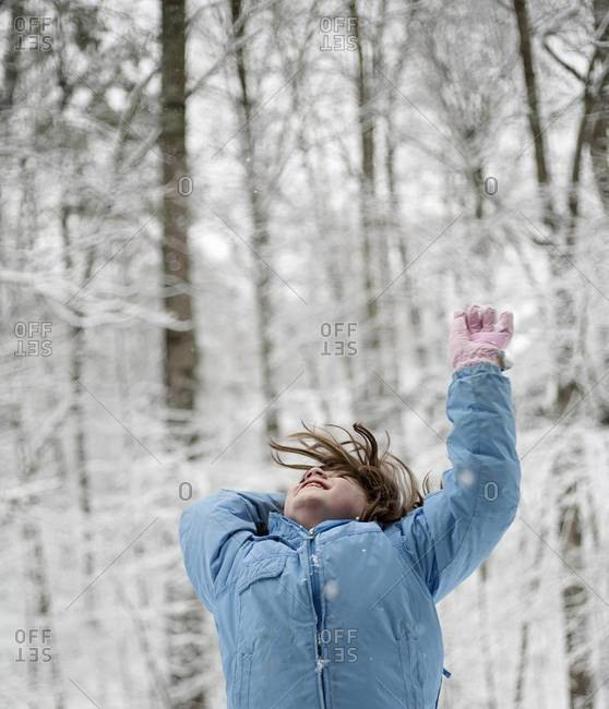 Girl throwing snow in the woods