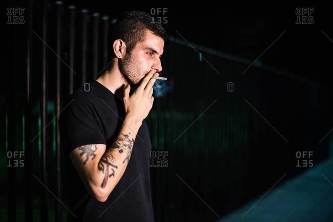 Young man smoking on a street at night at night