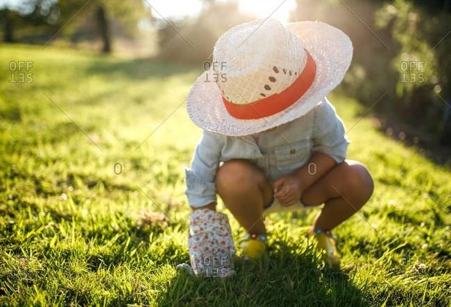 Little girl wearing straw hat crouching on a meadow