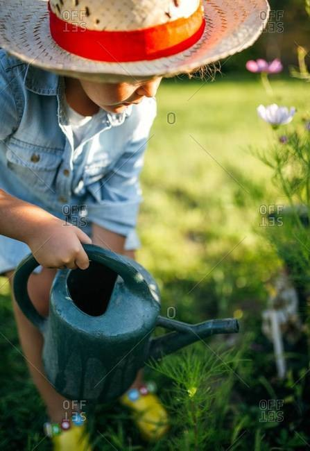 Little girl wearing straw hat watering flowers in the garden