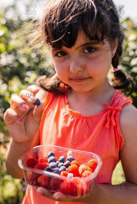 Portrait of little girl with plastic box of raspberries and blueberries