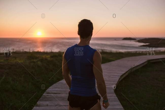 Back view of a jogger standing on boardwalk watching sunset