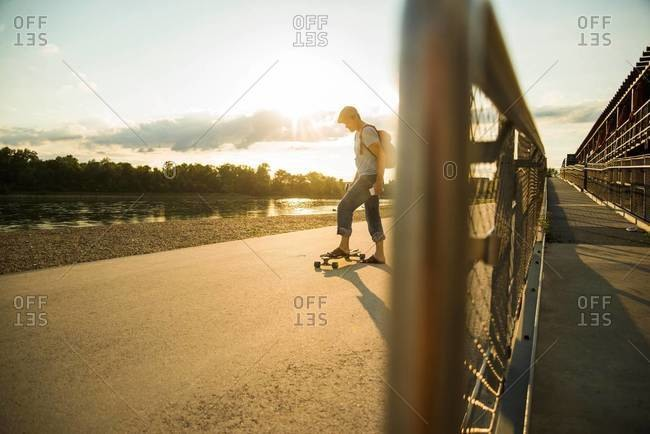 Man with skateboard at evening twilight