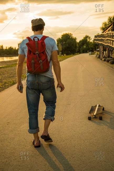 Back view of man with backpack and skateboard in the evening twilight