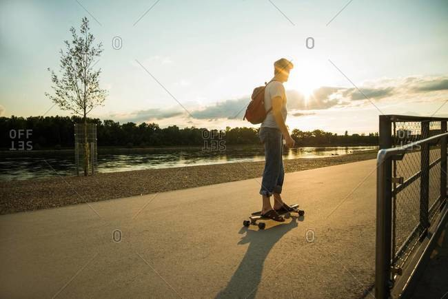 Man standing on skateboard in the evening twilight