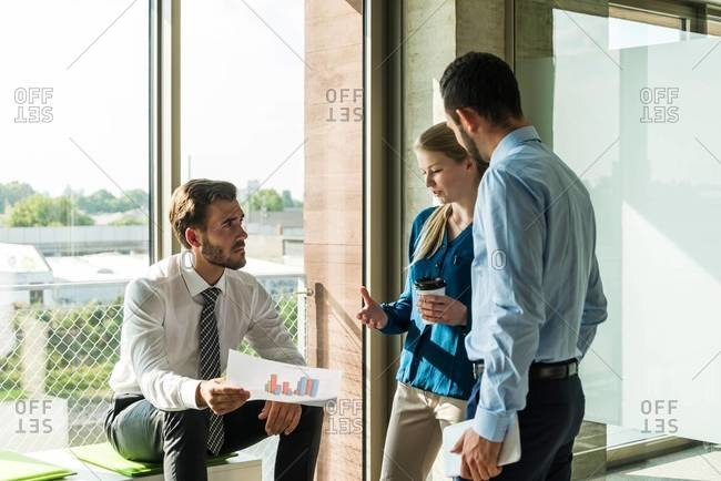Three young business people discussing document