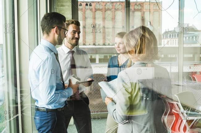 Business people with documents talking at the window