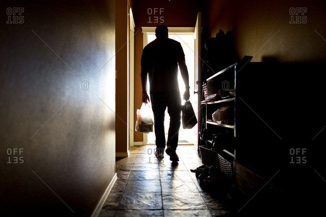Silhouette of man leaving house carrying bags