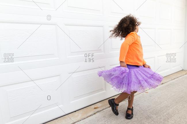 Girl in tulle skirt twirling by garage door