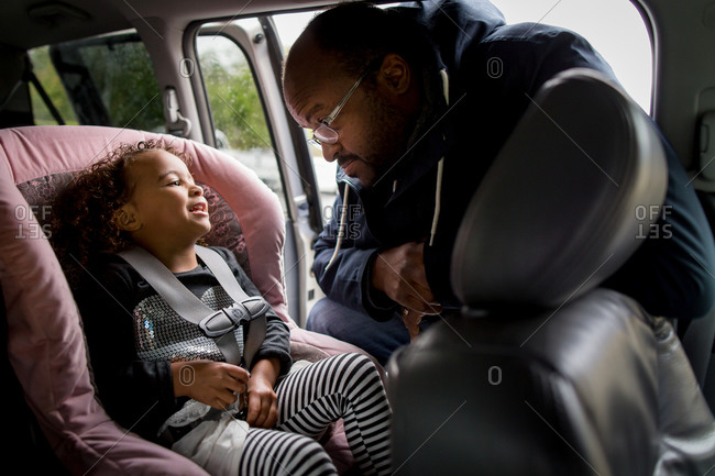 Dad buckling little girl into car seat
