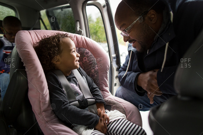 Dad buckling little girl up in car seat