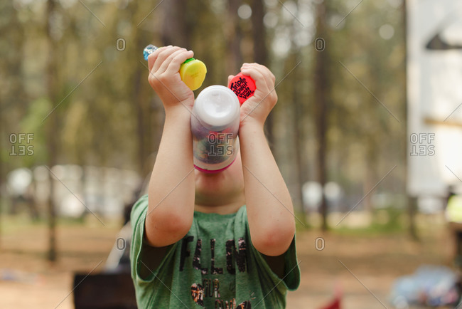Boy drinks water from bottle without using his hands