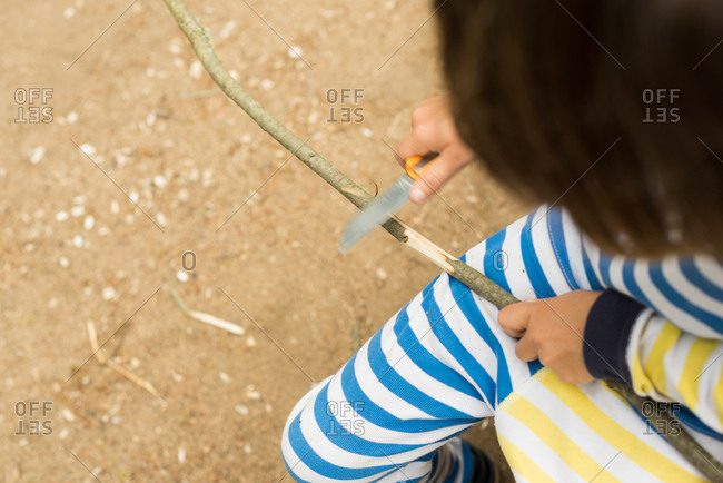 Overhead view of young child using a knife to peel bark off stick
