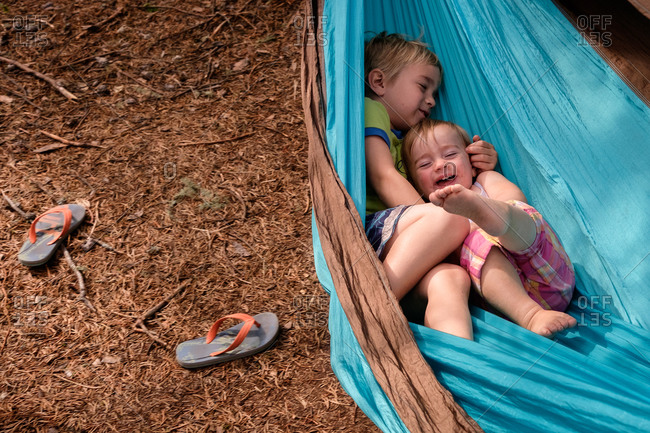Two young siblings play together in hammock