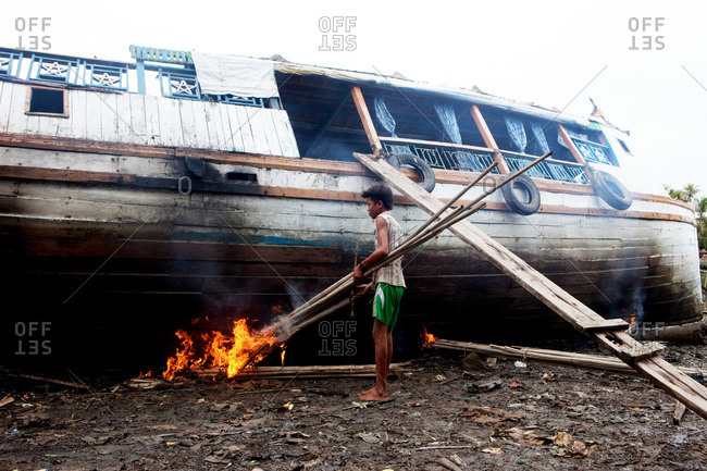 Mrauk U, Rakhine State, Myanmar - December 31, 2014: Boy lighting a fire under a wooden boat