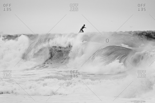 Surfer launching off large wave in California