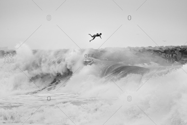Surfer launching from large wave in California