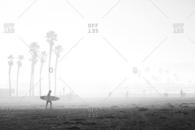 Surfer walking towards water on foggy California morning