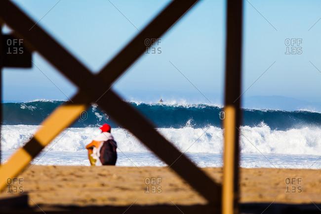 Man on California beach watching large waves