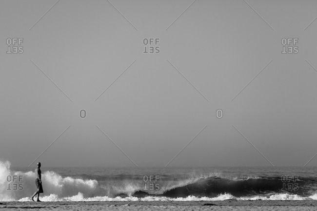 Man watches large wave break on California coast