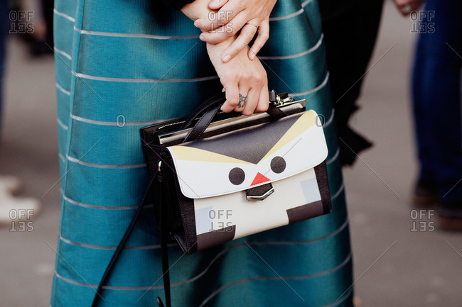 A woman carries a purse with a face on it