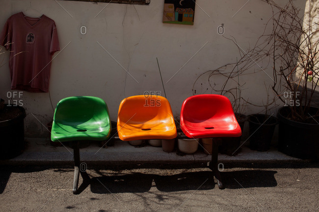 Three plastic chairs in a yard