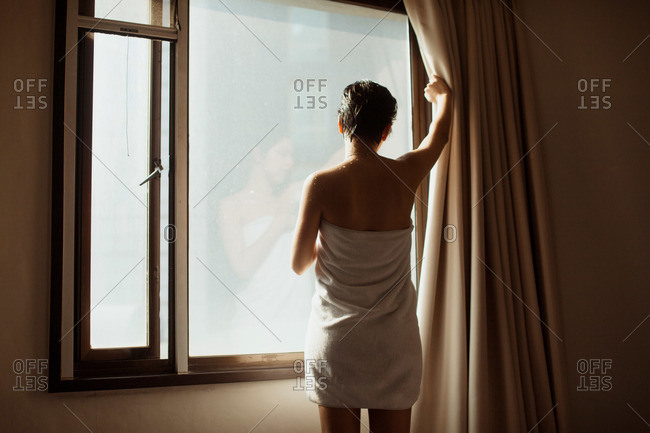 A young woman wrapped in a towel looks out the window