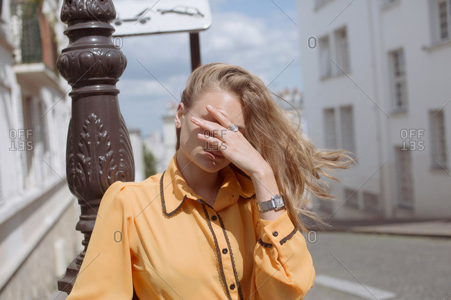 A woman on a street covers her eyes on a windy day