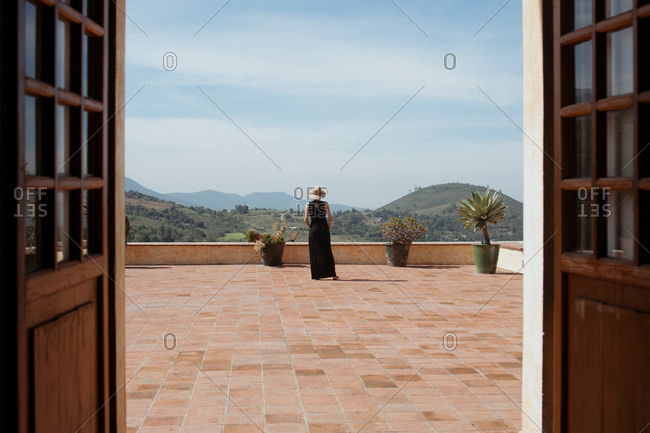 A woman on a balcony overlooking rolling hills