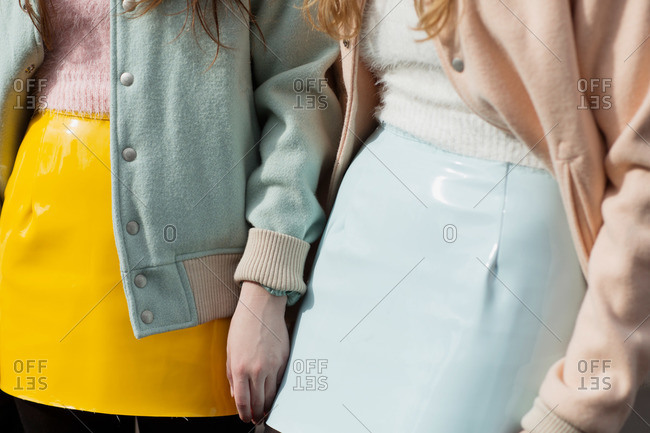 Two women wearing pastel clothing and shiny leather skirts
