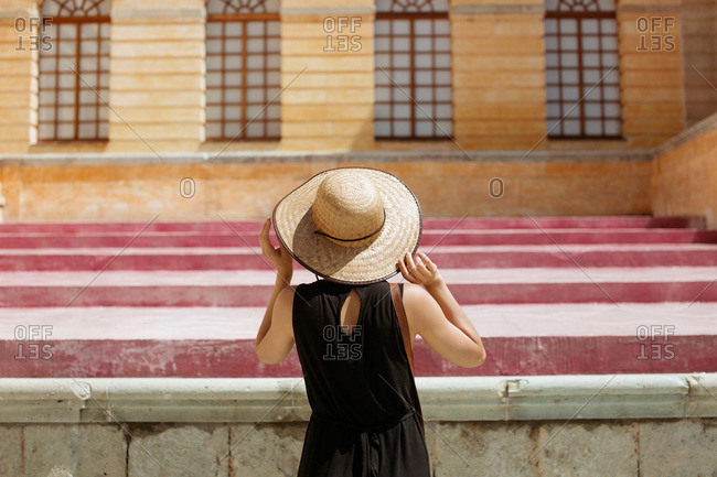 A woman in a straw hat admires the facade of a palazzo