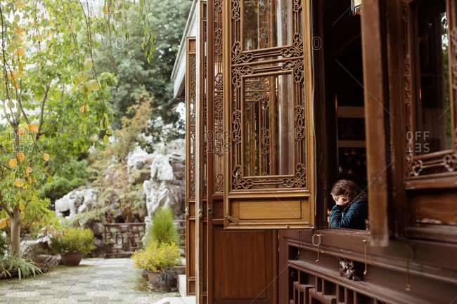 A girl leans out of a window into an Asian garden