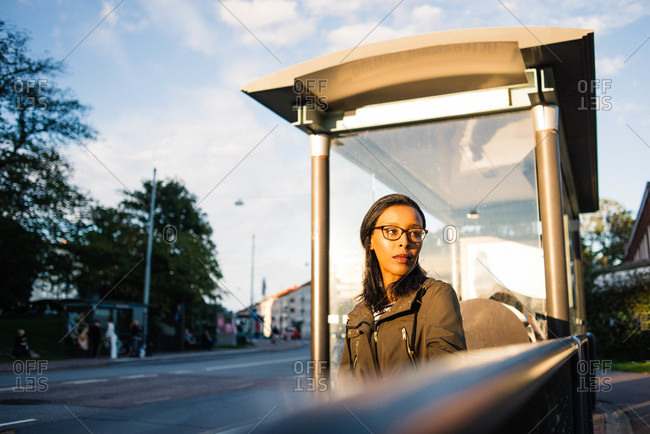 Woman sitting on a bench at a bus stop