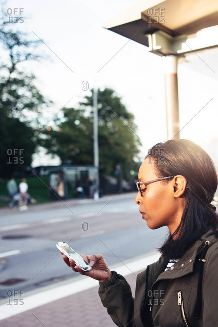 Woman checking her phone at a bus stop