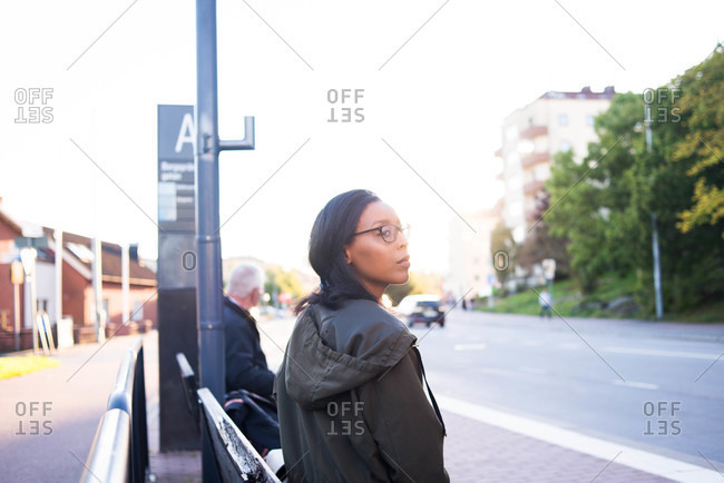 Woman waiting on a bench at a bus stop