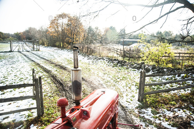 A red tractor driving into a frost covered field
