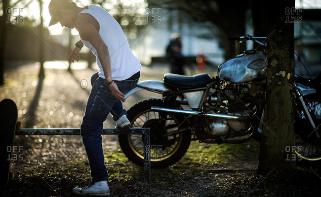 Teen boy standing on railing next to motorcycle