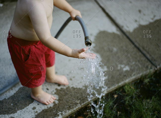Little boy catching water from a garden hose