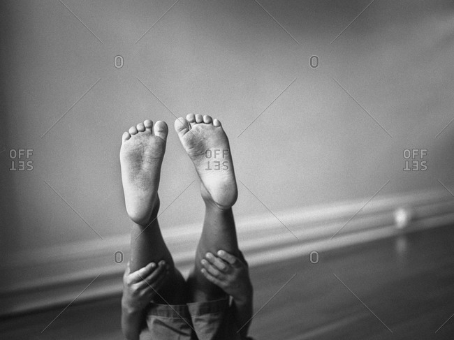 Feet of a little boy holding his legs up in the air
