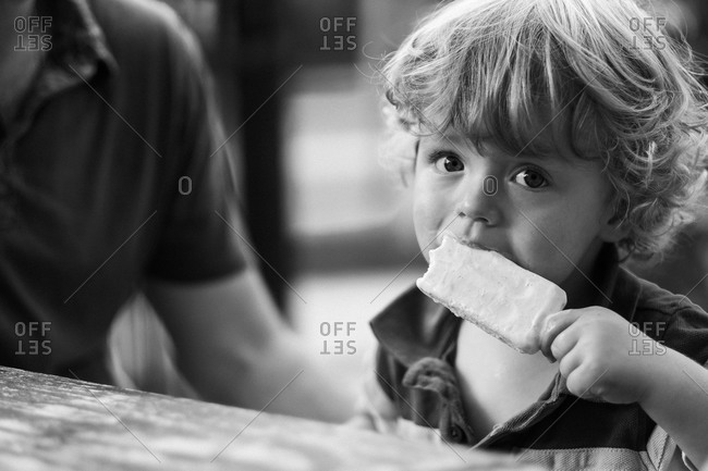 Little boy eating an ice cream popsicle