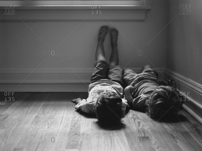 Brothers lying side by side against a wall