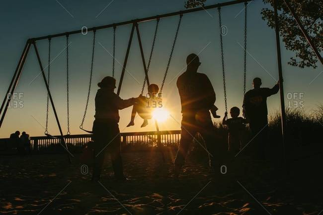 Kids swinging on swing set at dusk with adults