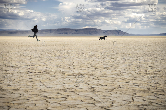Woman and her dog running in a desert of cracked sand