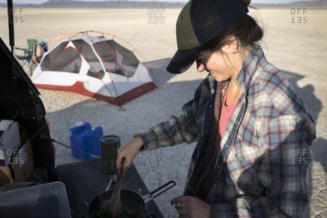 Woman cooking on a camp stove in a cracked sand desert