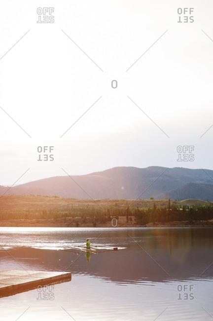 A woman kayaking at sunset